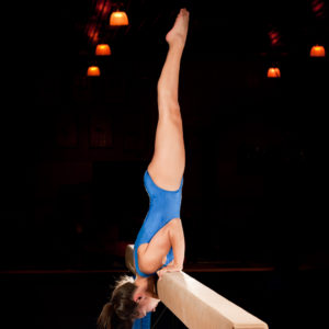 Female Gymnast Pauses In A Handstand On The Top Of Balance Beam Routine