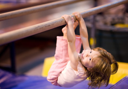"""Young girl, aged 2, proving it is never to early to start having fun and practicing good physical fitness. She is pulling herself up on uneven bars. Blue and yellow mats defocused in the background. Shallow DOF provides good subject isolation, focus on her eyes."""