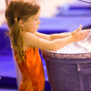 A young girl gymnast applying chalk to her hands before a bar routine. Powdered talc helps the hands grip yet slide around the bars.  This image is filled with action: crisp focuse on eye, with slight motion blur in hands as the girl claps them together and talcum powder flies.